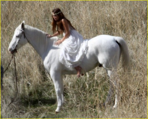 Fotos de Miley Cyrus montando un caballo blanco. Divertido