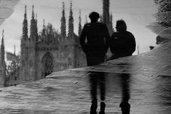 Do you remember the summer? (Donato Buccella / sibemolle) Tags: street people blackandwhite bw italy milan reflection love rain couple milano streetphotography duomo puddles malinconia pozzanghera canon400d absoluteblackandwhite rainingdays sibemolle truthandillusion