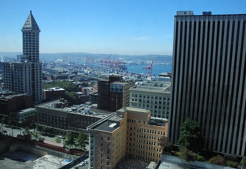 Smith Tower, skyscrapers, and a view of the Port of Seattle, orange cranes, on a sunny day, from the Columbia Tower, Seattle, Washington, USA by Wonderlane