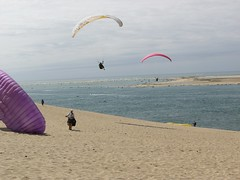 Stange Birds at the Great Dune of Pyla (traveling peter) Tags: ocean blue sky people france beach clouds outdoors island flying sand beige europe purple cloudy horizon dune gray bluewater overcast august atlantic paragliding 2008 atlanticocean graysky parachute bassin pyla aquitaine arachon gironde latestedebuch lebassin girondedepartment duneofpyla aquitaineregion year2008 ladunedupilat bassindarachon thegreatduneofpyla arachonbay