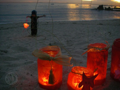 lanterns in the sand by the ocean
