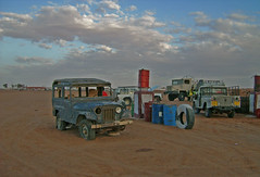 Gasstation_Westsahara (inlinguam) Tags: africa road street old sky cars sahara nature car yellow clouds vintage landscape evening algeria sand junk rust peace desert jeep poor wide scene gas gasstation workshop cj afrika oldtimer motive rough canoneos300d gravel wste oildrum tankstelle scarp westsahara werkstadt willys willysjeep