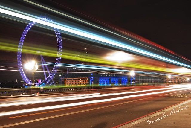 London eye at night through a Bus