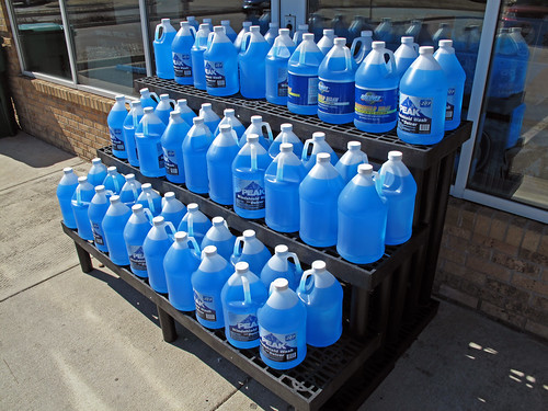 a merchandising display of blue wiper fluid