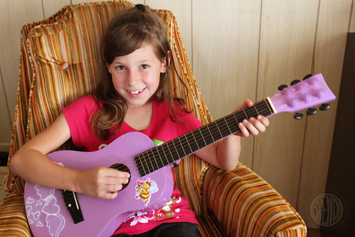 Girl playing a purple guitar