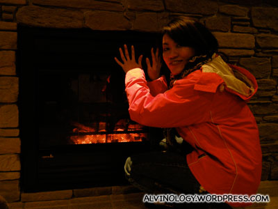 Rachel warming her at an electronic fireplace at the hotel lobby