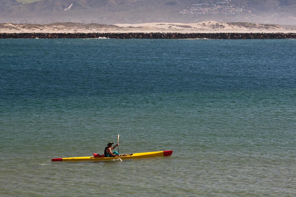 Lone Mark 1 kayaker (surf ski), near Morro Rock harbor entrance, south breakwater and sandspit shown, Morro Bay, CA