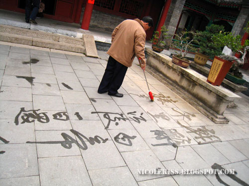 sifu writing calligraphy on floor