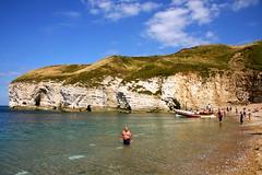 Fatboy Swim (Charles Frost) Tags: sea sky cliff man beach water clouds canon landscape eos coast boat sand stones fat yorkshire pebbles cave flamborough 40d