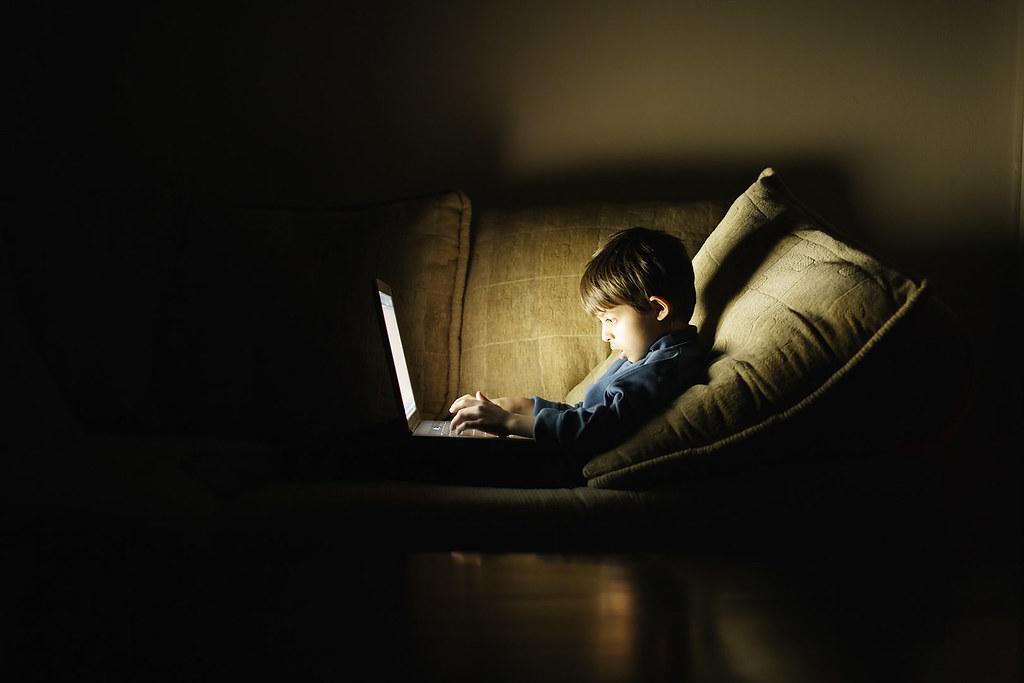 Boy using laptop computer in the dark