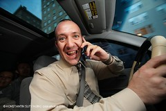 Businessman driving car and talking on cell phone. (Konstantin Sutyagin) Tags: auto life road camera new york city people urban white man motion male car mobile horizontal businessman shirt speed happy person one insane crazy unsafe automobile downtown driving phone looking steering angle action expression interior seat wide cell fast lifestyle tie talk cellular excited safety communication business busy american rush vehicle driver wireless inside conversation safe talking manager attention executive financial insurance communications seatbelt active exec multitasking caucasian trader moonroof workaholic transportraition