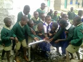 Børnene leger med og drikker vandet kort efter åbningen af brønden