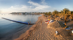 Naama Bay Sunrise panorama (WomEOS) Tags: bridge sky panorama holiday beach umbrella sunrise landscape redsea egypt sharmelsheikh hilton 2009 naamabay sharmelshaikh