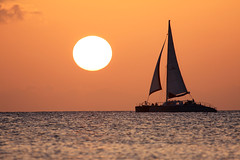 Red Sail Sports catamaran at sunset (Don McDougall) Tags: sunset sea sun reflection water sailing glare tour yacht horizon catamaran 100views sail caribbean 100 cayman caymanislands excursion glint grandcayman redsailsports mcdougall redsail donmcdougall
