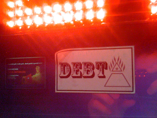 photo image of a poster with a triange that has the word debt on top.