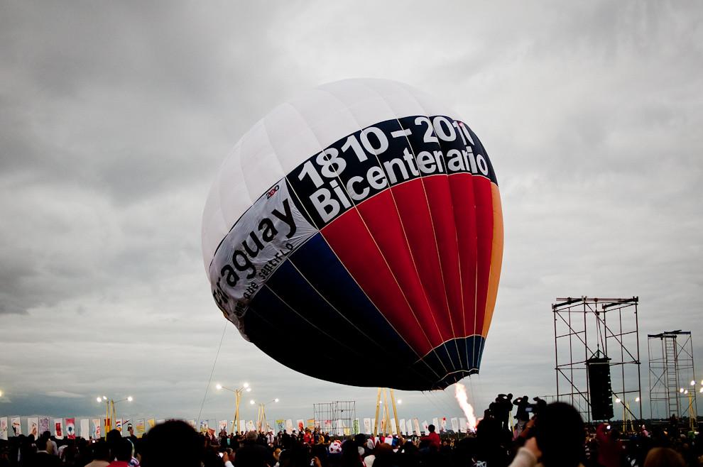 Un globo aerostático en su proceso de inflado con aire caliente se levanta sobre la multitud, este globo llamó la atención del publico debido a sus números, pero luego se aclaró que este globo fue fabricado para los festejos del Bicentenario Argentino 1810-2010.  (Elton Núñez - Asunción, Paraguay)