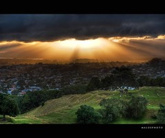 Throwing some light on the suburbs (Mark Emirali) Tags: trees light newzealand cloud sun yellow canon dark landscape intense view auckland nz suburbs rays burst onetreehill copyrighted cornwallpark canon30d pleasedonotusewithoutmypermission maloe4 maloephoto maloephotography markemirali markemiraliphotography