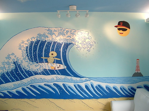 A photograph of a mural depicting a cute cartoon turtle riding a surfboard on a big wave