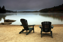 Where Did The Summer Go? (Megan Lorenz) Tags: autumn lake ontario canada fall beach nature water landscape outdoors still sand chair scenery published view scenic peaceful whitney getty summerfun adirondackchair gettyimage muskokachair lakeoftworivers algonquinprovincialpark singhray the4elements meganlorenz killarneylodge mlorenzphotography