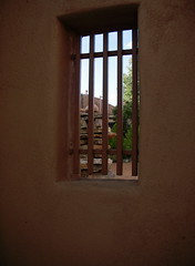 Through a window... (lorises) Tags: santafe window redwall adobewall adobestructure plazaarea