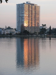 Lake Merritt high rise with its windows a blaze across the lake