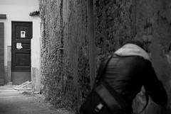 Between darkness and light (crocketpocket) Tags: door light bw man black wall fix bag photo nikon darkness d100 cartello vicolo pioggia luce fotografo città divieto azione oscurità betwen istante