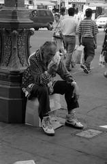 Pensive (cyan79) Tags: california ca people bw man slr cars film 35mm la blackwhite losangeles traffic pentax box cigarette crowd broadway oldman jacket carton ilford fila pentaxzxm universal400 ilforduniversal400