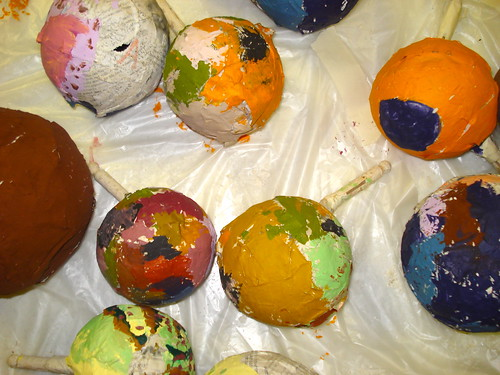 The arts and crafts table is covered in colorfully painted paper-mache balls, made by campers.