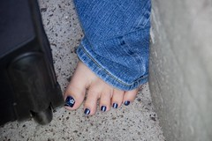 As long as I'm doing close-up shots I might as well toss in this one.  I did the tattoos on her feet too but you can't see them very well when she's wearing jeans. (colorblindPICASO) Tags: california blue closeup sarah concrete foot airport dof ground luggage barefoot denim sandiegoca sandiegocomiccon bluepolish rollingluggage comiccon2009