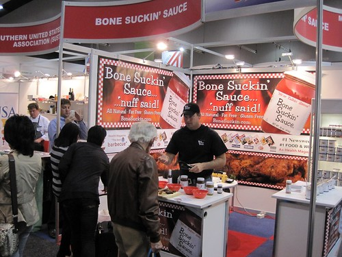Pat Ford of Ford's Gourmet Foods shares the company's signature Bone Suckin' Barbeque Sauce with visitors to a food show in Australia. Thanks in part to support from FAS market development programs, Ford's now exports to more than 50 countries and 35 percent of their sales come from international markets.  (Photo courtesy of FAS)