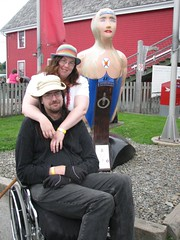 A white woman (Anna), sunburned and tired looking, stands behind a white man (Don), also sunburned and tired looking, in a manual wheelchair.  They are posed in front of a wooden figurehead of a mermaid