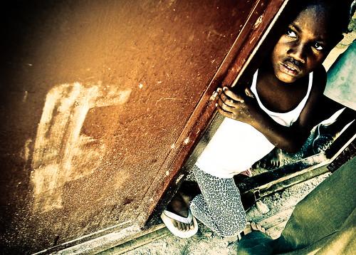 Un niño haitiano se asoma desde un orfanato esperando recibir ayuda