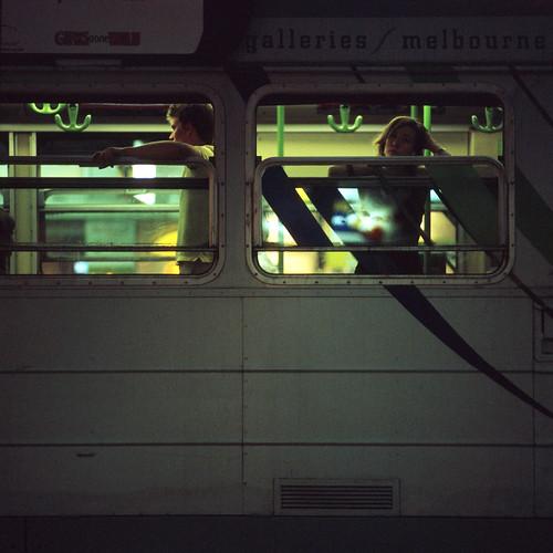 Fotografía de dos personas aparentemente no conectadas entre si asomadas en las ventanas de un vagón de tren en la noche