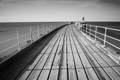 pier (black and white) (tricky (rick harrison)) Tags: ocean wood sunset shadow sea wall pier wooden still fishing long shadows fishermen harbour curves calm deck whitby rails curve beacon railings decking sweep sweeping ruleofthirds leadinglines leadingline