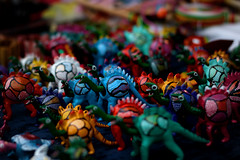 Colorful Danger (matthileo) Tags: blue red music orange blur color macro green colors toy toys miniature rainbow focus dof dinosaur michiganstateuniversity michigan msu august mini depthoffield eastlansing folkmusic dinosaurs michiganstate streetvendor prismatic greatlakesfolkfestival msumuseum glff canonef50mmf18ii michiganstateuniversitymuseum 08072009 7august2009 michigantraditionalartsprogram nattywallpaper