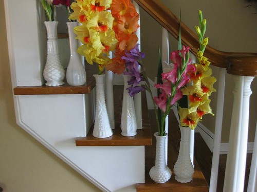 Stairwell displays collection of tall white milkglass vases, via Flickr: jenscloset
