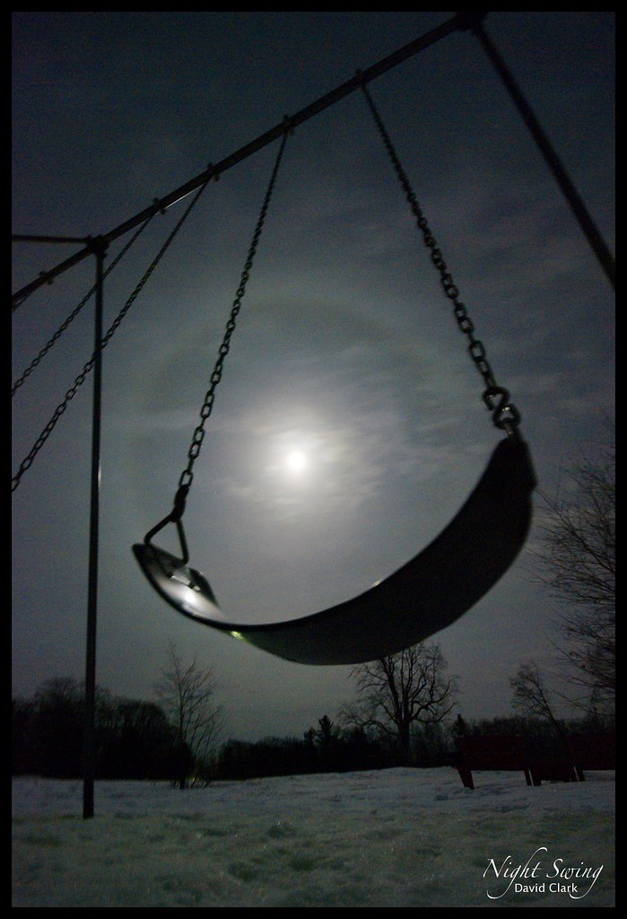 A swing, seen in wide angle from below, with the full moon showing through.