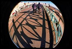 promenading (BoblyP) Tags: uk england film 35mm brighton shadows unitedkingdom betty multipleexposure promenade filmcamera seafront eastsussex promenading 400asa lowsun supershot adifferentpointofview lomofisheye2 boblyp brightsunshin