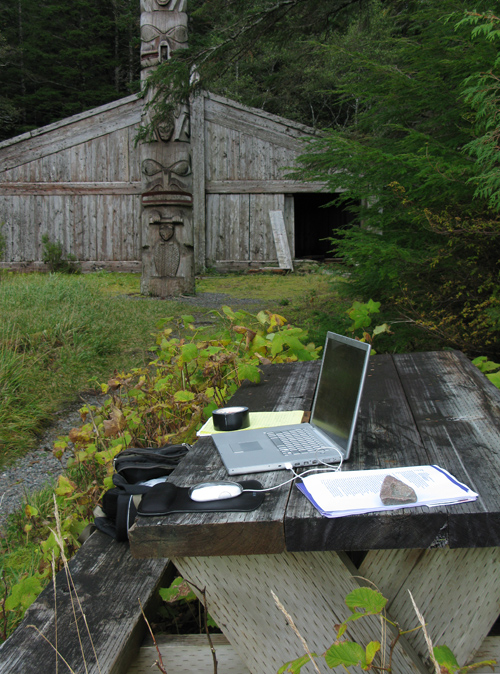 laptop on picnic table near Chief Son-i-Hat's Whale House, Kasaan, Alaska