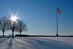 Rising Hope (fluxxus1) Tags: blue winter light shadow red sky usa sun white snow black tree cemetery silhouette backlight america stars landscape geotagged lumix hope back memorial war europe peace shadows belgium crystal stripes flag banner perspective panasonic explore american change obama veterans henrichapelle onblue barackobama barack blueribbonwinner flickrsbest mywinners skytheme lx3 flickrdiamond simplyperfect lumixaward goldstaraward spiritofphotography