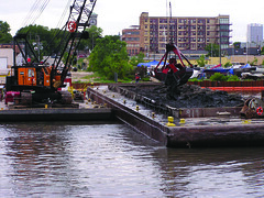 A crane drops contaminated sediment from the bottom of the Kinnickinnic River onto a barge. The sediment will be transported to the Milwaukee Confined Disposal Facility on Jones Island. ~photo Jennifer Yauck