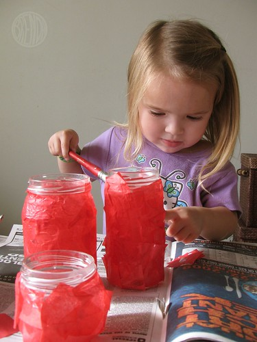 child decoupaging glass jars