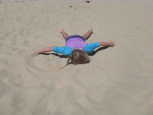 Caitlin making sand angels