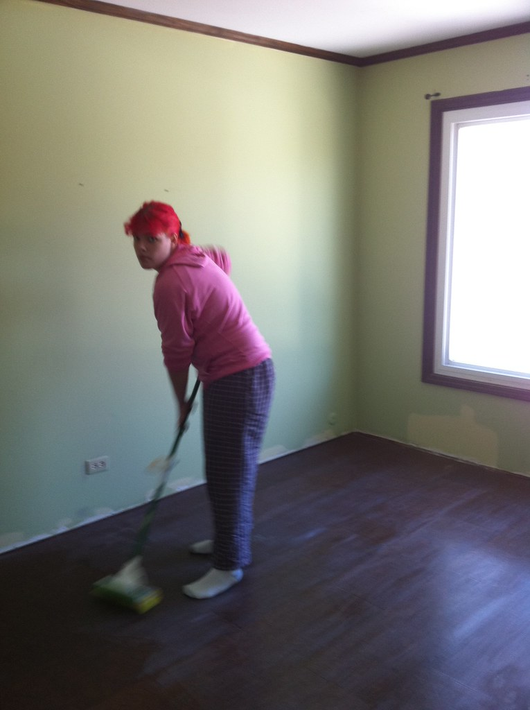 Heather, prepping cork floor for next layer of Varathane.