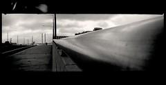 extended recession (mugley) Tags: city bridge urban blackandwhite bw panorama film 35mm cityscape pavement toycamera lofi australia melbourne victoria lightleak sidewalk negative xp2 epson docklands 135 railing footpath ilford urbanlandscape lampposts tramwires c41 latrobest v700 blackbars haking ilfordxp2super400 ilfordxp2400super port1010 lomophobia plasticpanocamera newquaytowers boltebridgepylons