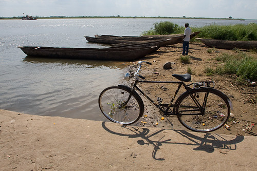Hand dug canoes sit in the water of the Zambezi. Bike in foreground. ph: Esther Havens