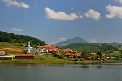 Village of Orlan, Lake Batllava, in eastern Kosovo, July 18, 2009 (Ivan S. Abrams) Tags: sky clouds rural landscape hope nikon europe peace village muslim islam faith scenic happiness scene mosque kosova kosovo balkans nikkor pastoral rebirth renaissance mosques reconstruction contentment southerneurope kfor kosove unmik exyugoslavia orlan southeasteurope tranquuility onlythebestare ivansabrams nikond700 nikon24120mmf3556gvr exserbia lakebatllava lakebatlava nikkor24120mmf35mmf3556gvr abramsandmcdanielinternationallawandeconomicdiplomacy ivansabramsarizonaattorney ivansabramsbauniversityofpittsburghjduniversityofpittsburghllmuniversityofarizonainternationallawyer