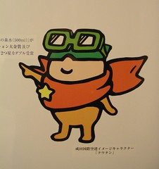 kutan, cute mascot for narita airport, wearing goggles and scarf pointing to mineral water details, side of vending machine, narita airport, tokyo (kejhu) Tags: cute water japan scarf japanese tokyo design airport graphic character cartoon goggles mascot mineral narita kutan