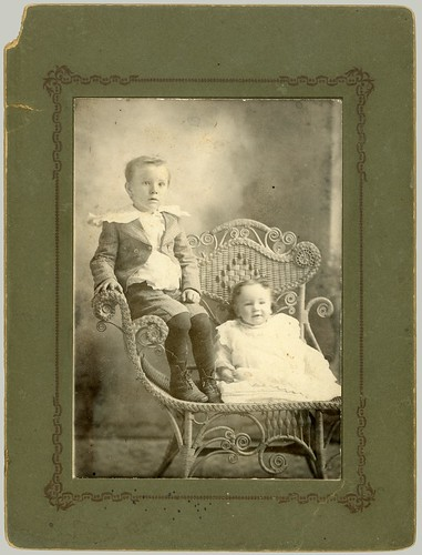 Two children and a one arm chair