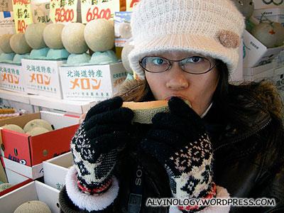 Rachel enjoying a single slice of Japanese muskmelon